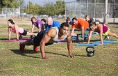 stock photo of boot camp  - Group of adults exercising in outdoor boot camp - JPG