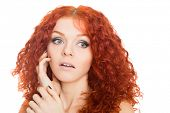 Beautiful red haired girl with a surprised look isolated on white.