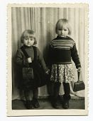 KURSK, USSR - CIRCA 1950s: An antique photo shows studio portrait of a two little sisters.