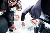 Asian business people in group structuring deal on flipchart