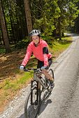 Woman mountain biking in sunny forest cycling path smiling