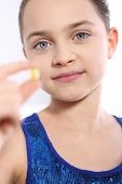 Caucasian girl holding a yellow pill