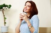 Thoughtful woman holding cup with coffee at home