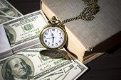 Still Life Image Of Pocket Watch On Bills And Old Book