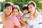 stock photo of 7-year-old  - Portrait Of Asian Family Enjoying Walk In Summer Countryside - JPG