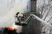 Firefighters Extinguishing Fire On Hydraulic Crane Platform