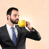 Young Businessman Drinking A Coffee Over Ocher Background