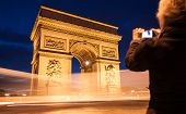 stock photo of charles de gaulle  - Tourist taking photos of the Arc de Triomphe in Paris France at twilight with traffic light trails - JPG