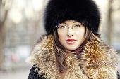 stock photo of ermine  - Winter style girl wearing fur hat and glasses in the city park - JPG