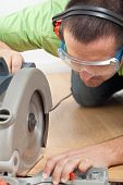 picture of laminate  - Man cutting laminate floor plank with electrical circular saw - closeup