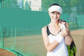 image of late 20s  - Happy and Positive Female Tennis Woman Holding Tennis Mesh Bag with Lots of Balls - JPG