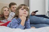 Family watching TV in bedroom