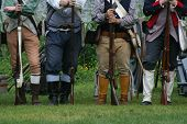 Picture of colonial militiamen stand at ease during a revolutionary war reenactment.
