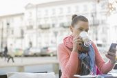 Young woman drinking coffee while using cell phone at sidewalk cafe