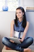 Pretty young girl listening music on tablet PC through headset, smiling.