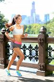 Running woman jogging to music in New York City, Central Park, Manhattan. Runner wearing earphones and armband for smart phone. Female fitness jogger training outside for healthy lifestyle.