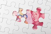 Incomplete puzzle over chinese yuan banknote background
