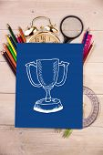 Winners cup against students desk with blue page