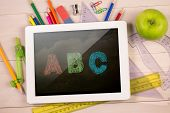 Composite image of digital tablet on students desk showing abc
