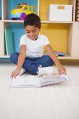 Cute little boy sitting on floor reading in classroom at the nursery school