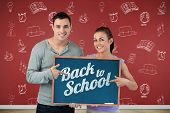 Smiling young couple pointing at sign they are holding against blackboard on wooden board