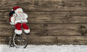 Wooden Christmas Background With Santa On A Bike. Funny Greeting Card For Xmas.