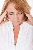 Middle aged woman suffers from headache.