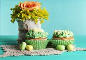 Tasty cupcakes on table, on turquoise background