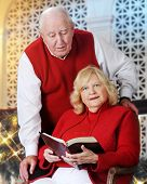 A senior woman reading the Bible with her husband looking on over her shoulder.  They're in a Christmas-decorated room.