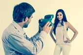 Handsome young man taking photos of beautiful girl with instant camera