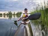 foto of collins  - senior paddler in a racing sea kayak  on a calm lake - JPG