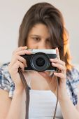 Pretty brunette looking at retro camera on couch at home in the living room