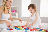 Side view of mother and daughter playing with building blocks on bed at home