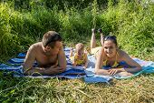 Young Family Mom Dad And Child Outdoors On A  Summer Day Are Tanning