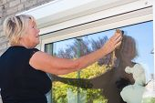 stock photo of window washing  - Dutch retired senior Woman washing small window on the outside of her home shot close up - JPG