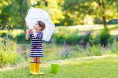 Adorable Little Girl In Yellow Rain Boots And Umbrella In Summer Park