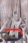 Magnet and wrenches on color wooden background