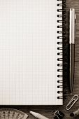 notebook and office accessories on wood background