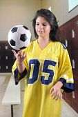 A pretty teen girl in an over-sized jersey in a locker room.  She's attempting to balance a soccer ball on one finger.