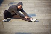 Portrait of young sportsman doing stretching exercise outside