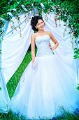 foto of wedding arch  - Beautiful elegant asian bride stands under the wedding arch - JPG