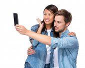 Asian girl and caucasian boy take selfie