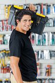 Side view portrait of smiling man carrying toolbox on shoulder in hardware store