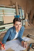Portrait of confident female carpenter drawing on blueprint at table in workshop