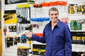 Portrait of smiling worker in overalls gesturing in hardware store