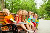 Kids with blue notebooks sit in row on bench