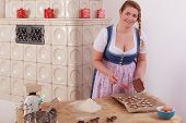 Young woman covering Cookies with chocolate.