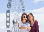 stock photo of funfair  - two young girls taking selfie at the funfair - JPG