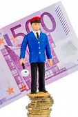 railway worker on money stack symbol photo for early retirement, costs for rail