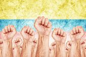 stock photo of labourer  - Columbia Labour movement workers union strike concept with male fists raised in the air fighting for their rights Columbian national flag in out of focus background - JPG